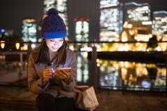 Mujer que usa el teléfono móvil en la noche en la ciudad de Yokohama Fotos de archivo libres de regalías