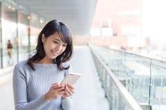 Mujer que usa el teléfono móvil en pasillo de estación Imágenes de archivo libres de regalías