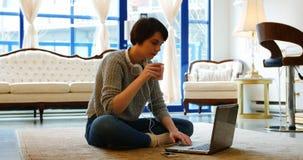 Mujer que usa el teléfono móvil en sala de estar almacen de video
