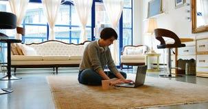 Mujer que usa el teléfono móvil en sala de estar metrajes