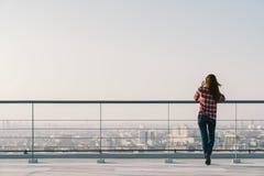 Mujer que usa el teléfono móvil en el tejado durante puesta del sol con el espacio de la copia, la comunicación o el concepto sol foto de archivo libre de regalías