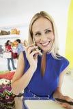 Mujer que usa el teléfono móvil en tienda Fotos de archivo