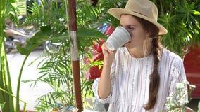 Mujer que usa el teléfono móvil mientras que bebe té al aire libre metrajes