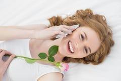 Mujer que usa el teléfono móvil mientras que subió la reclinación en cama con Fotos de archivo libres de regalías