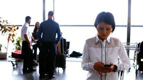 Mujer que usa el teléfono móvil mientras que viajeros que obran recíprocamente con uno a almacen de video