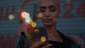 Mujer que usa el teléfono móvil rodeado por efecto del bokeh almacen de metraje de vídeo