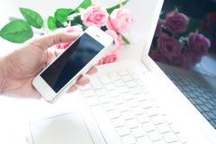 Mujer que usa el teléfono móvil y el ordenador portátil con la rosa del rosa imagenes de archivo