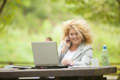 Mujer que usa el teléfono móvil y la computadora portátil en oficina abierta Fotografía de archivo