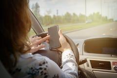 Mujer que usa el teléfono mientras que conduce el coche fotografía de archivo