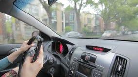 Mujer que usa el teléfono mientras que conduce metrajes