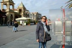 Mujer que usa el teléfono público Imagen de archivo