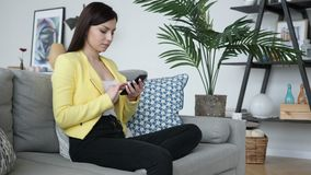 Mujer que usa el teléfono para hojear en línea mientras que se sienta en el sofá almacen de video