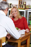 Mujer que usa el teléfono en restaurante Fotos de archivo libres de regalías