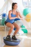 Mujer que usa en amaestrador del balance en la gimnasia Fotos de archivo libres de regalías