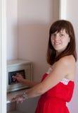 Mujer que usa la caja fuerte en la habitación fotos de archivo