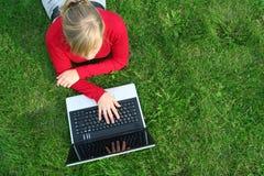 Mujer que usa la computadora portátil al aire libre Imagen de archivo libre de regalías