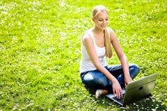 Mujer que usa la computadora portátil al aire libre Fotos de archivo libres de regalías