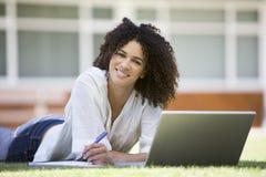 Mujer que usa la computadora portátil en campus Fotos de archivo