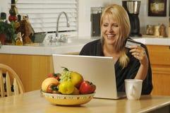 Mujer que usa la computadora portátil en cocina Foto de archivo libre de regalías