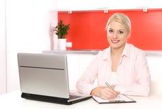 Mujer que usa la computadora portátil en cocina Imágenes de archivo libres de regalías