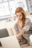 Mujer que usa la computadora portátil en el sofá Foto de archivo