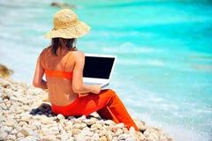 Mujer que usa la computadora portátil en la playa Imagen de archivo