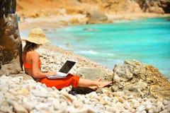 Mujer que usa la computadora portátil en la playa Imágenes de archivo libres de regalías