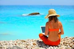 Mujer que usa la computadora portátil en la playa Fotos de archivo