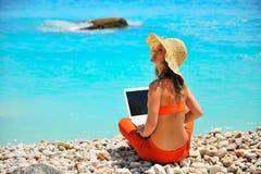 Mujer que usa la computadora portátil en la playa Foto de archivo