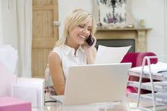 Mujer que usa la computadora portátil y hablando en el teléfono imagen de archivo