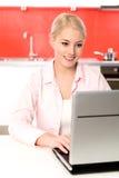 Mujer que usa la computadora portátil en cocina Fotos de archivo libres de regalías