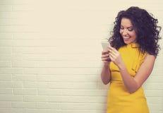 Mujer que usa la conexión a internet de alta velocidad que manda un SMS en el teléfono elegante fotografía de archivo