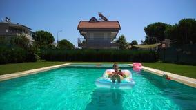 Mujer que usa la crema de la protección solar y mintiendo en el flotador de la piscina almacen de metraje de vídeo
