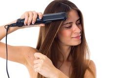 Mujer que usa a la enderezadora del pelo Fotos de archivo libres de regalías