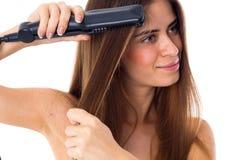 Mujer que usa a la enderezadora del pelo Imagenes de archivo