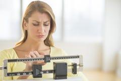 Mujer que usa la escala del peso de balanza en el gimnasio Fotografía de archivo