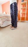 Mujer que usa la escala en dormitorio Fotografía de archivo