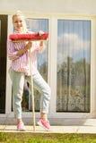 Mujer que usa la escoba para limpiar el patio del patio trasero Fotografía de archivo libre de regalías
