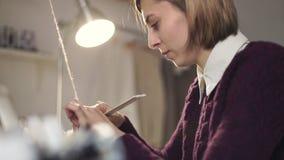 Mujer que usa la herramienta para tirar del hilo en telar metrajes