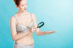 Mujer que usa la lupa para examinar su piel de los topos Imagen de archivo