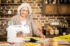 Mujer que usa la máquina de coser foto de archivo