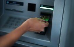 Mujer que usa la máquina de las actividades bancarias Fotos de archivo