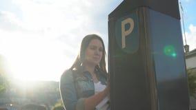 Mujer que usa la m?quina del estacionamiento en la calle metrajes