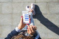 Mujer que usa la mensajería inmediata app en el teléfono móvil imagen de archivo