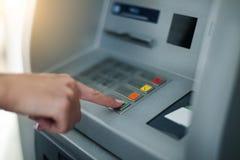 Mujer que usa la máquina de las actividades bancarias Fotografía de archivo libre de regalías