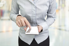 Mujer que usa la pantalla táctil del finger elegante del teléfono Imagen de archivo libre de regalías