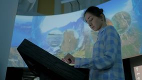 Mujer que usa la pantalla táctil interactiva en el museo de la historia moderna almacen de video