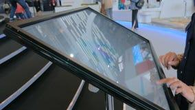 Mujer que usa la pantalla táctil interactiva en la exposición urbana almacen de metraje de vídeo