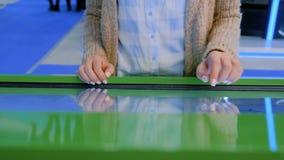Mujer que usa la pantalla t?ctil interactiva en el museo moderno metrajes