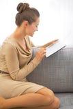Mujer que usa la PC de la tableta mientras que se sienta en el diván fotografía de archivo